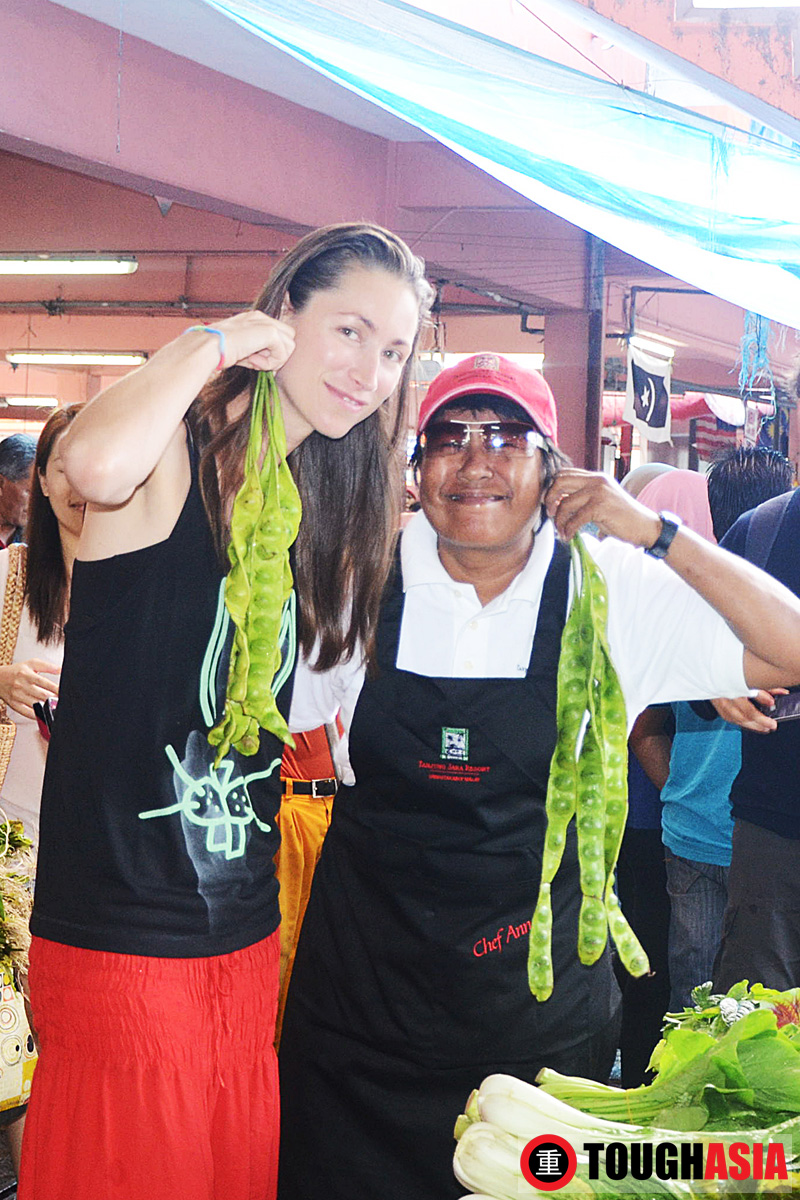 Tara Stiles (left) and Chef Ann clowning around with petai as earrings at the morning market.