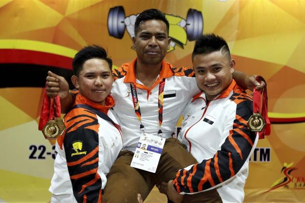 Young Malaysian weightlifing champs, Fatin Amira (left) and Khairul Anuar hoist their coach in appreciation after their record breaking wins at SUKMA recently. (The Star)